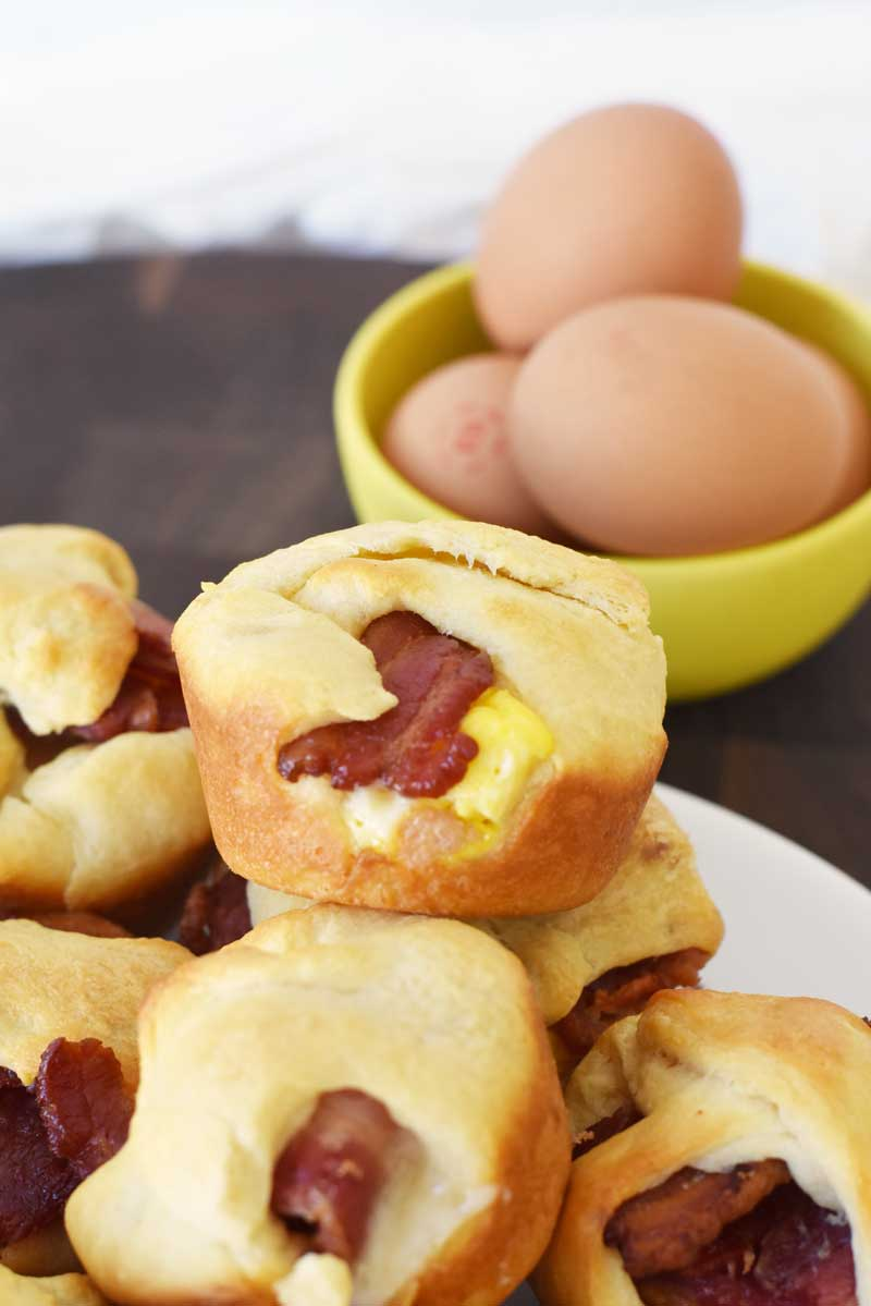 Bacon Egg and Cheese Crescent Bites made in a muffin tin. There are eggs in a yellow bowl in the shot to the right.