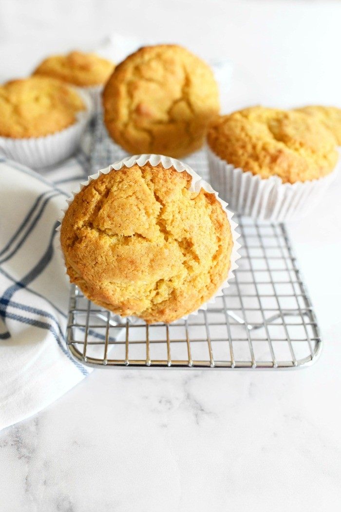 Bakery Style Jumbo Corn Muffins on a silver baking rack. There is a striped napkin in the shot as well.