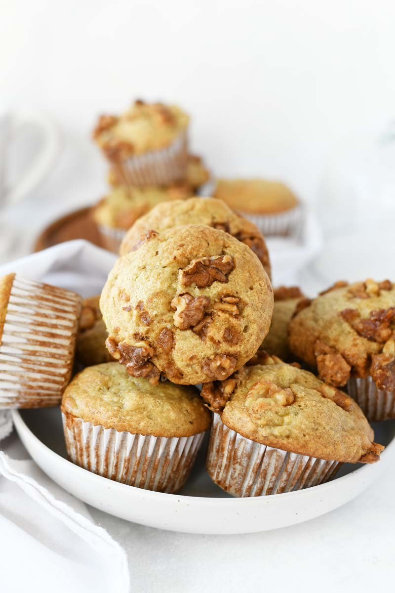 Banana Bread Muffins with Candied Walnuts stacked on top of each other on a white plate.