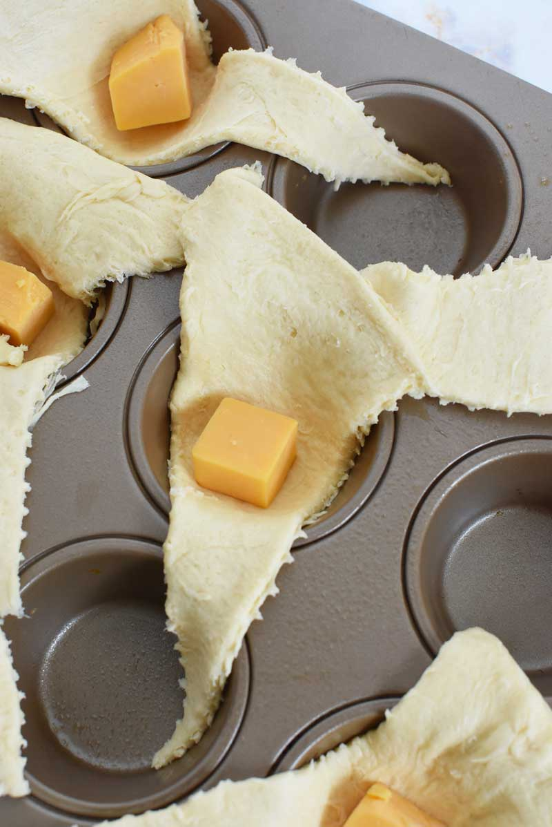 Cheddar cheese cubes in crescent dough triangles nestled in a muffin tin.