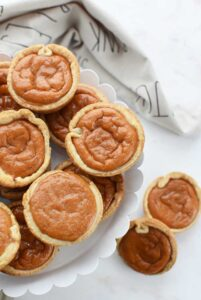Easy Pumpkin Pies Made in a muffin tin are on a white stand.