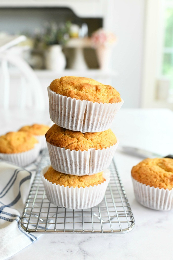 Jumbo Honey Corn Muffins stacked on a silver baking rack. There are two muffins also in this shot.