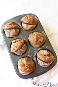Jumbo Pumpkin Muffins with Cinnamon + Sugar in a grey muffin tin. There is a white baking towel nearby.