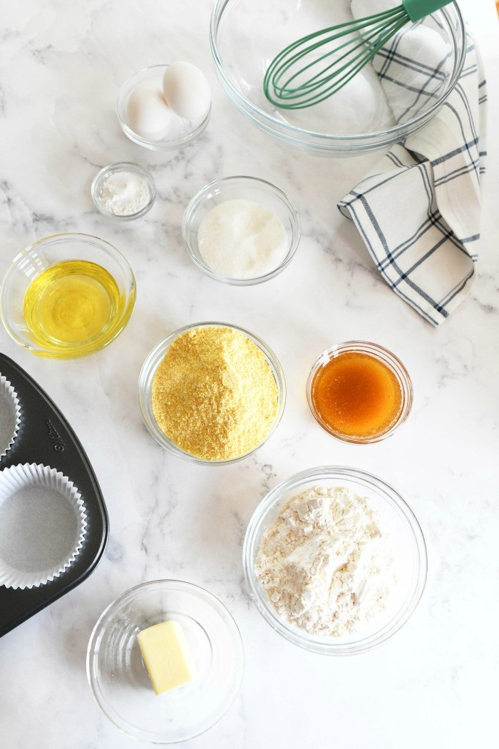 Jumbo corn muffins ingredients on a white marble table with a blue patterned napkin.