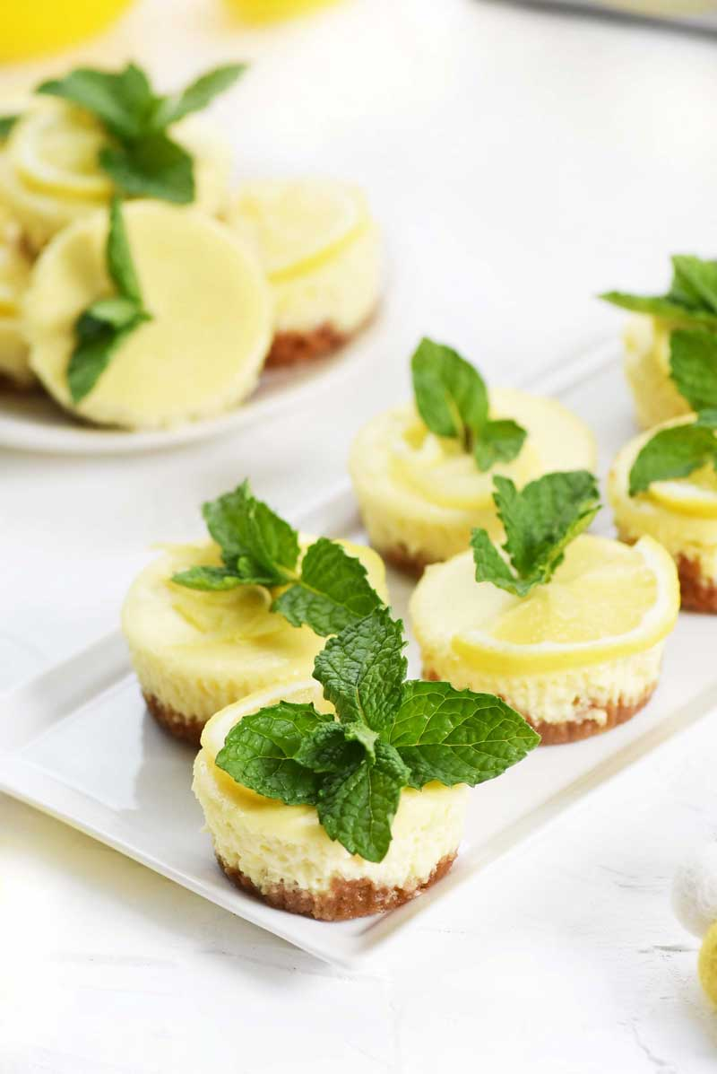 Mini Muffin Tin Cheesecakes with lemon and mint leaves on a white dish.