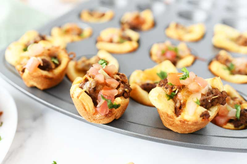 Mini Taco cups made in a muffin tin. These are sitting on top of a silver muffin tin.