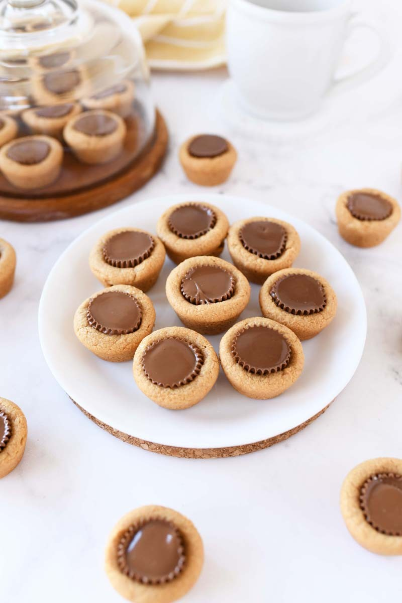 Mini Peanut Butter Cup Cookies on a white table and scattered around.