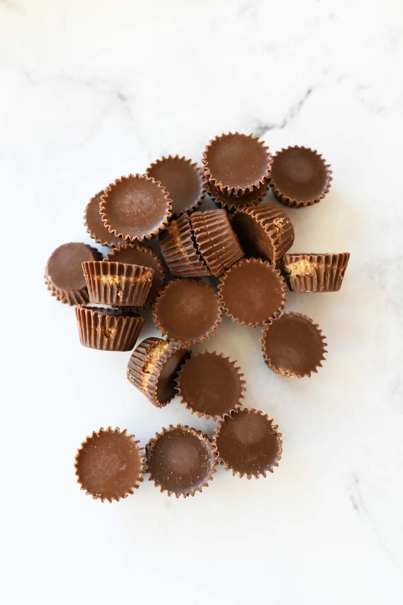 Mini Peanut Butter Cups unwrapped on a white marble table.