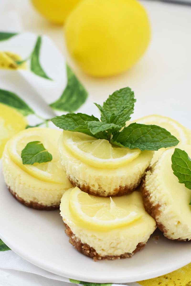 Mini Lemon cheesecakes are stacked on a white plate. These muffin tin cheesecakes have mint and lemon slices on them.