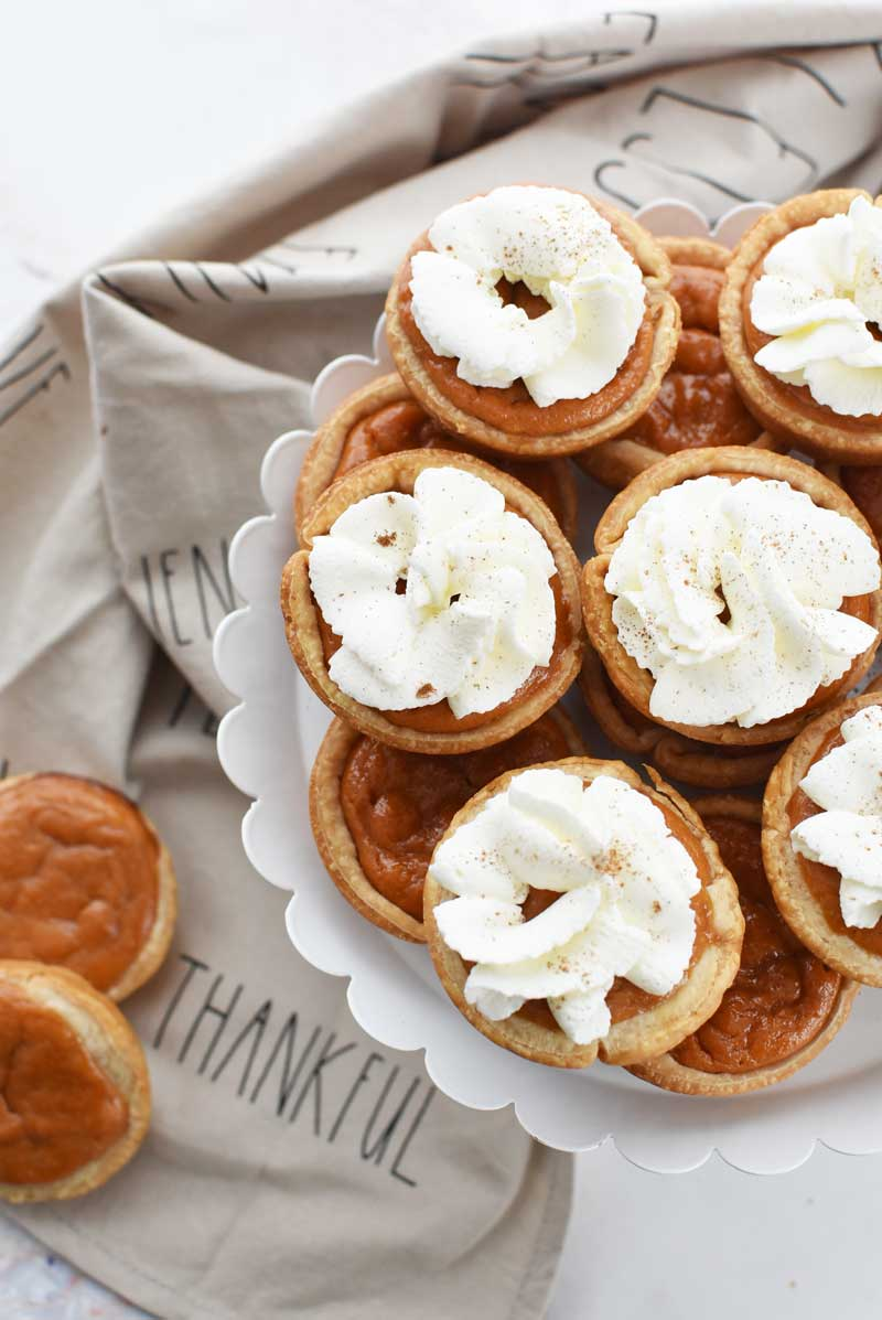 Muffin Tin pumpkin pies are served with whipped cream and cinnamon on a white, scalloped cake stand.