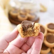 Hand holding a peanut butter cookie with a peanut butter cup baked inside a mini muffin tin with one bite taken out of it.
