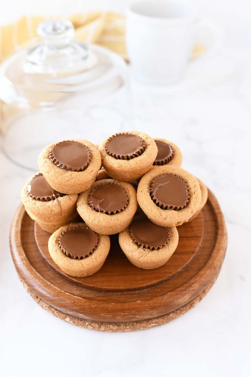 Peanut butter cookie cups in a glass cake holder.