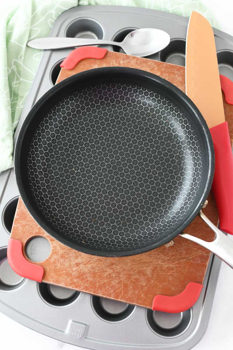 Various supplies used to make mini crescent tacos. Featured is a small black skillet, red wooden cutting board, mini muffin tin, and a spoon.