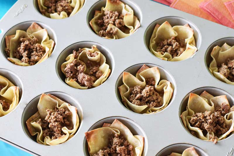 Taco meat is filled in baked wonton cups. They are in a silver muffin tin on a blue table.