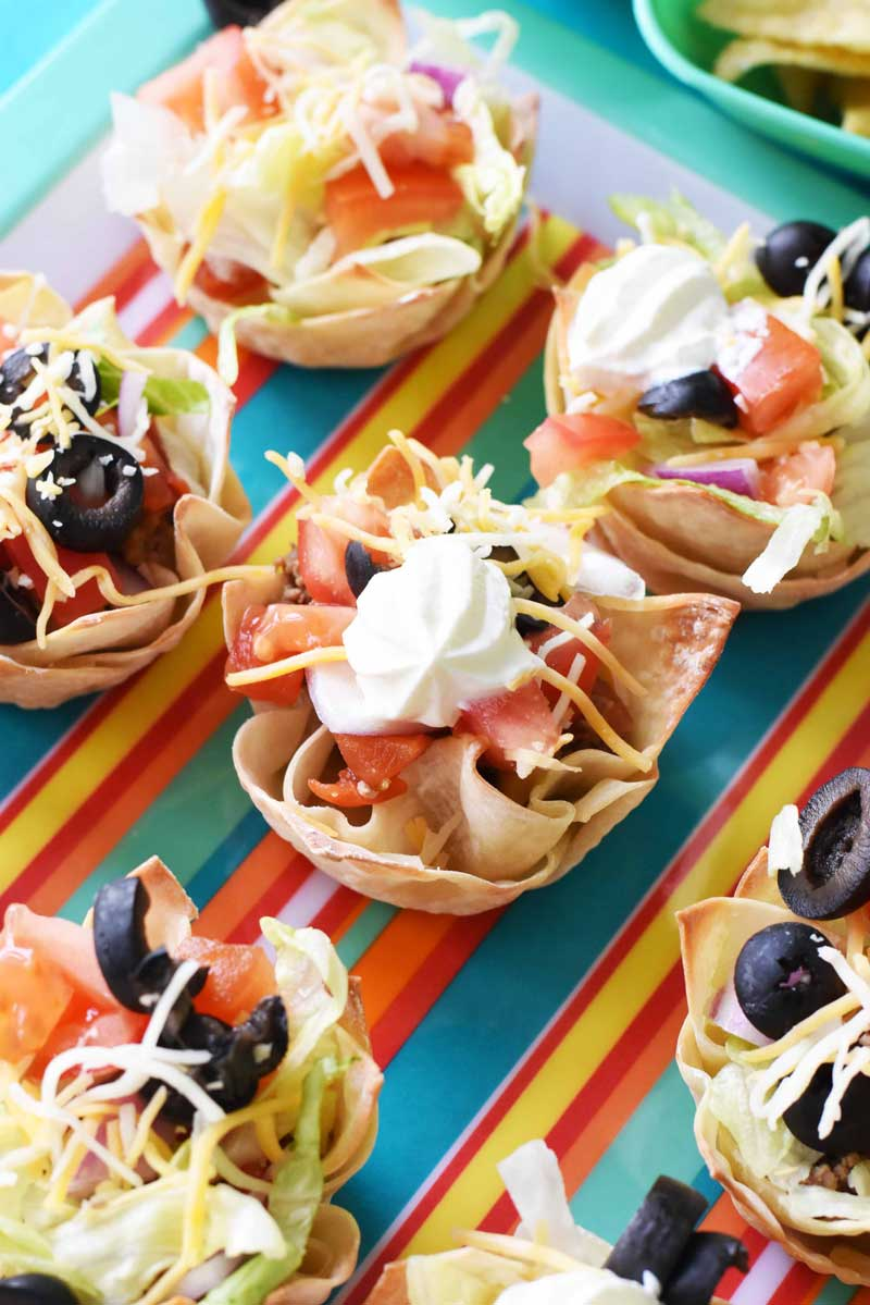 Wonton Taco cups are loaded with filling like ground beef, sour cream, cheese, olives, lettuce, and more! They are on a multi-colored, striped platter on a blue table.