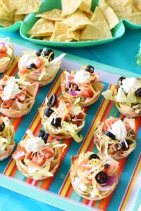 Fully loaded wonton tacos are on a striped, multi-colored platter. There are blue bowls with corn chips in the background.