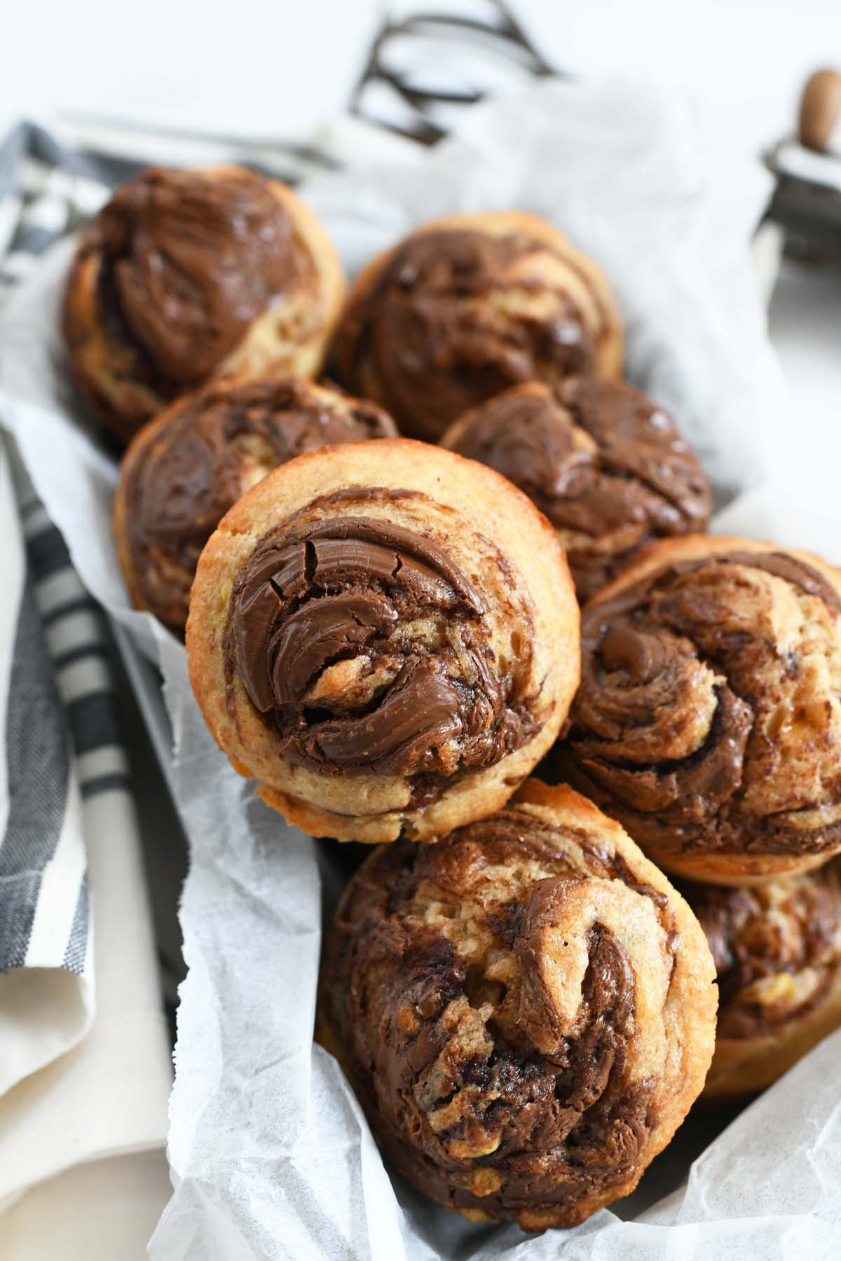 Banana Hazelnut muffins recipe in a parchment lined pan. there is a striped napkin nearby.