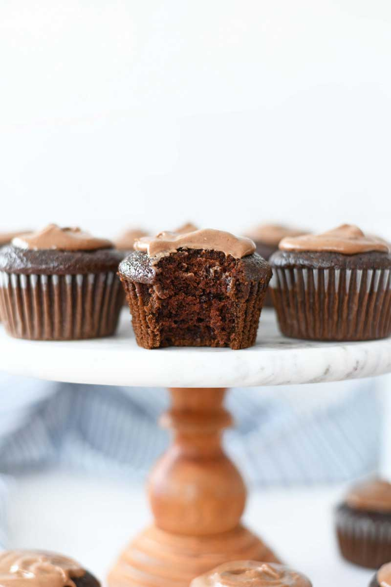 Chocolate frosted cupcakes are on a marble and wood cake stand. A bite is taken out of the middle of the cake.