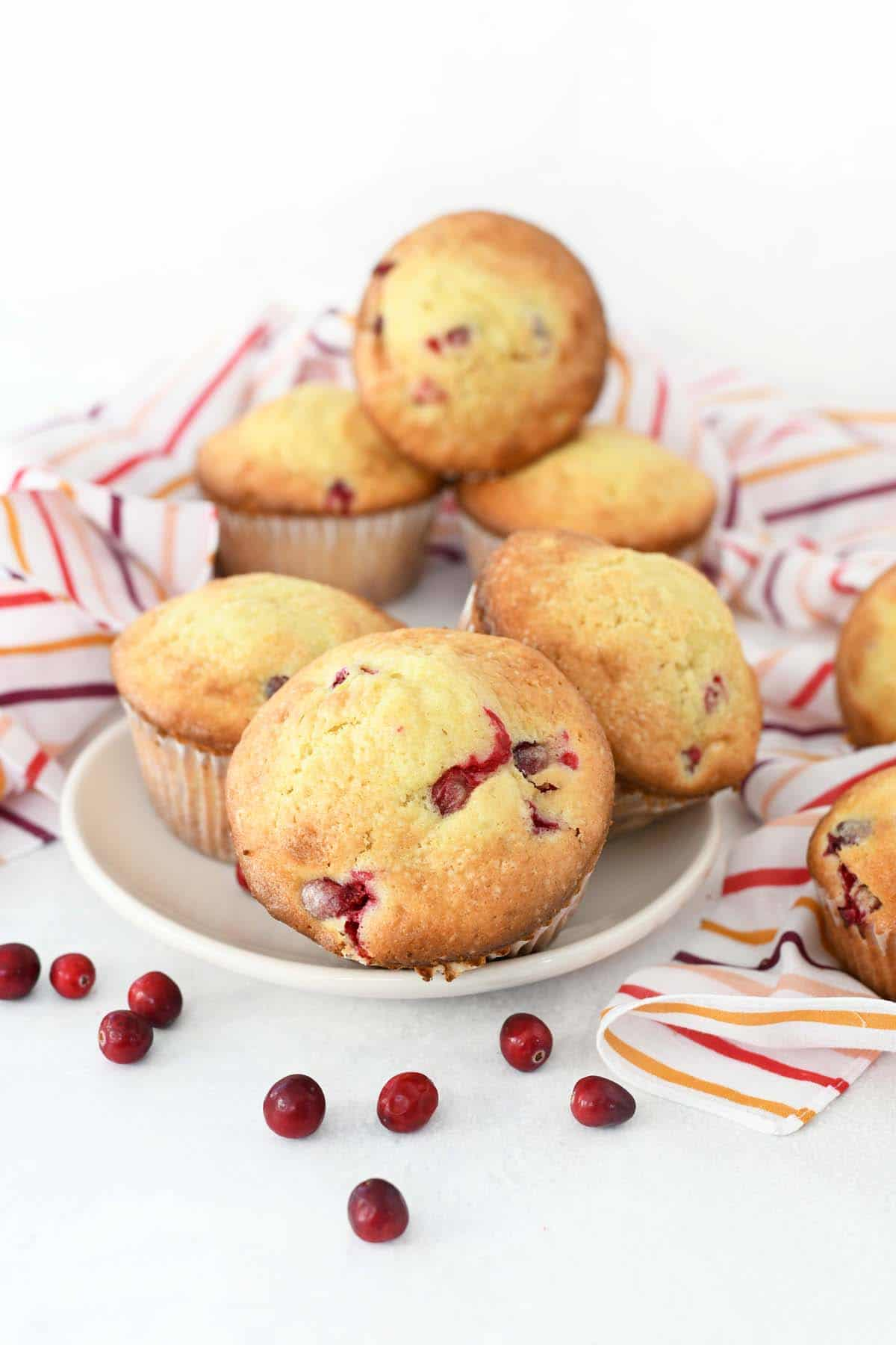 Cranberry Orange Muffins in a bowl with striped napkins and whole cranberries.