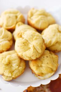 Garlic Cheese Bread Crescent Bites- Baked until golden-brown in a muffin tin. These are stacked on a white cake stand.