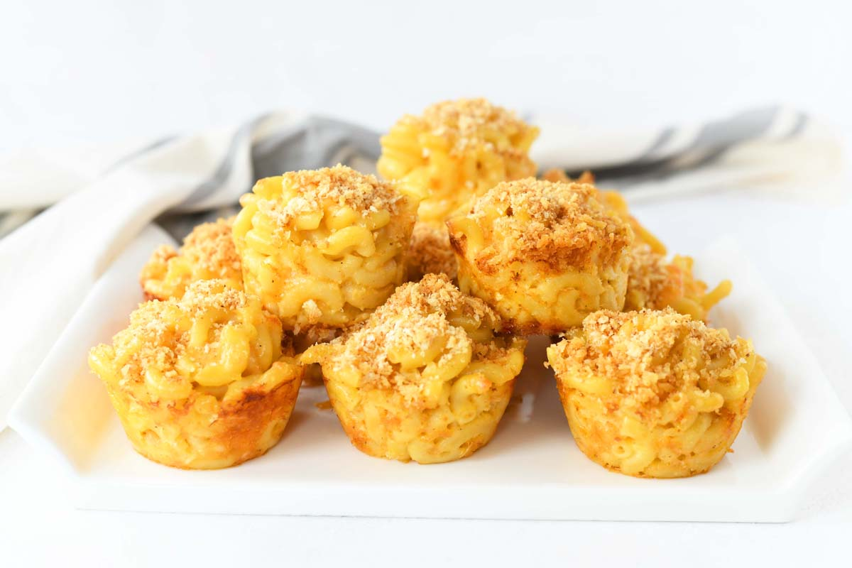 Macaroni and Cheese Muffins are stacked in a pyramid shape on a white platter.