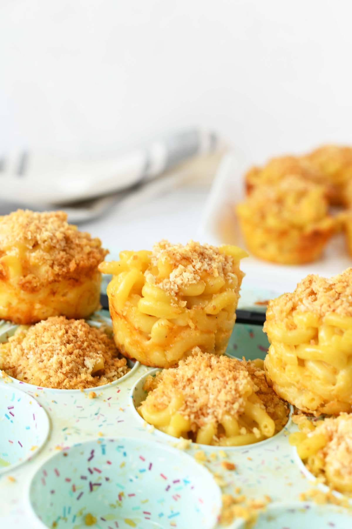 Macaroni and Cheese in a Muffin Tin. Muffin cups are on a blue silicone pan.