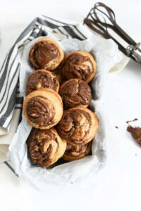Nutella Banana Swirl Muffins in a parchment-lined pan. There is an old-fashioned hand mixer in the background and a grey and tan striped napkin.