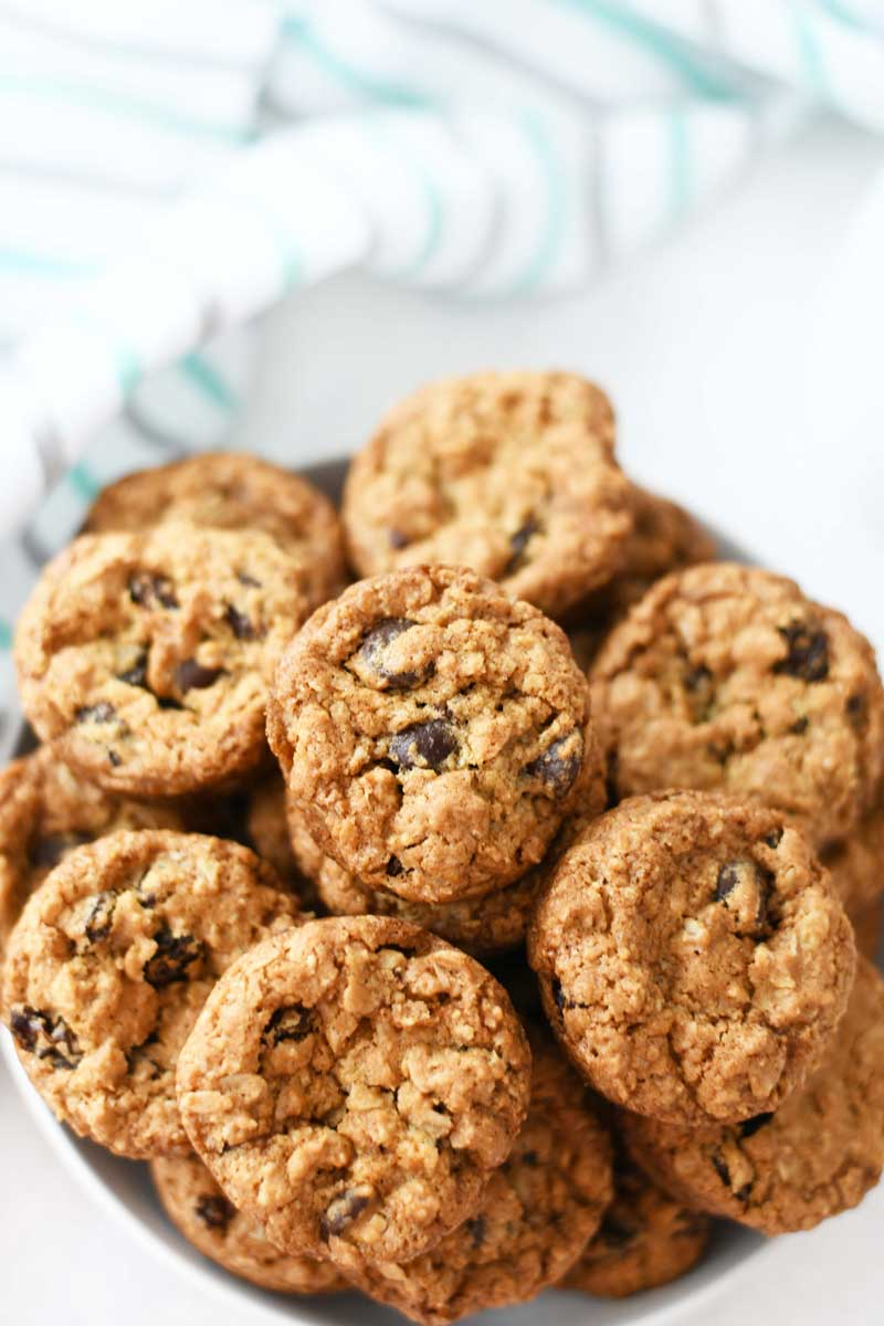 Oatmeal Raisin Cookies are golden brown in a white dish up close.