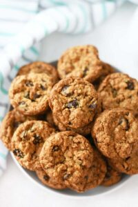 Oatmeal Raisin Cookies Made in a Muffin tin. These cookies are stacked in a white bowl.