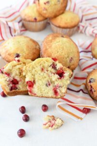 Orange Cranberry Muffins Recipe on a white table with cranberries and striped napkins.