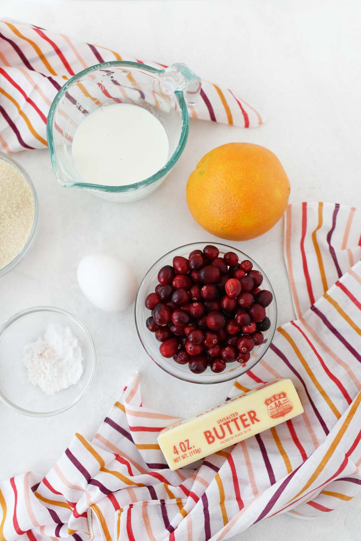 Orange cranberry muffin ingredients on a white table with a colorful striped napkin.