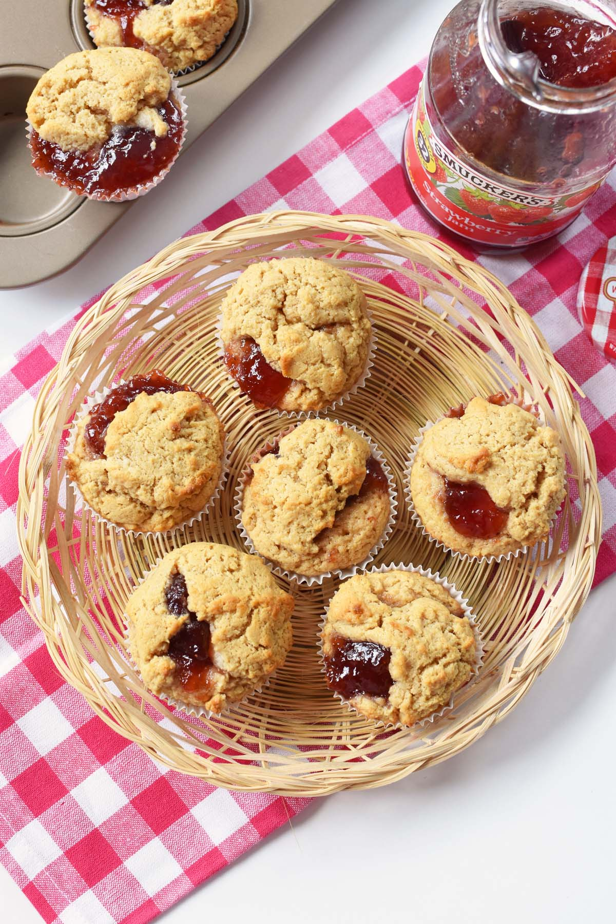 Peanut Butter & Jelly Muffins are in a wicker basket with a red plaid napkin, muffin tin, and Smucker's Strawberry Jam jar.