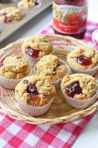 Peanut Butter and Jelly Muffin in a wicker basket with a red, plaid napkin. There is a jar of Smucker's Jam in the background.