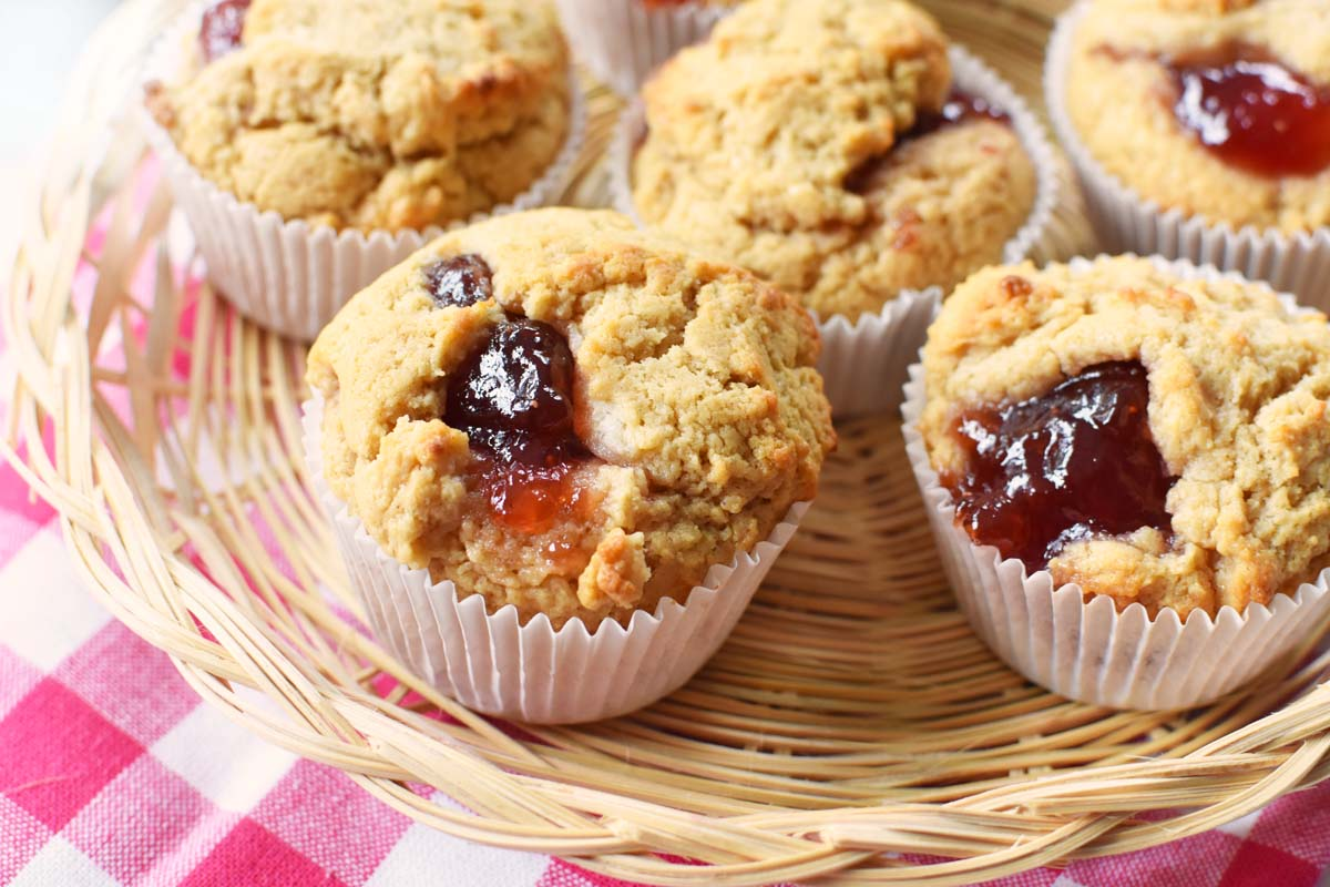 Peanut Butter and Strawberry Jelly Muffins in a wicker basket with a red plaid napkin.