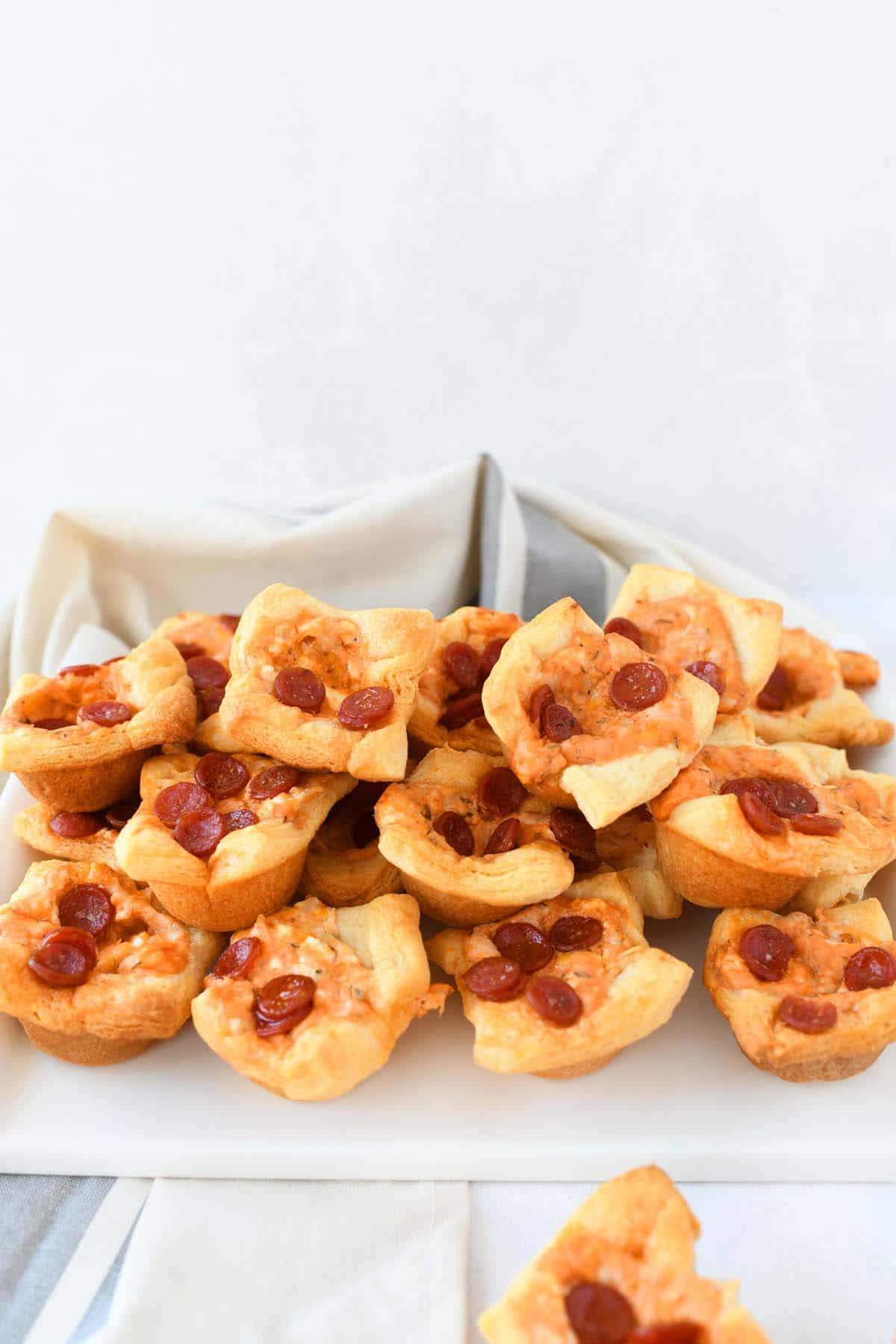 Pepperoni Pizza bites on a white tray with a tan napkin in the shot.