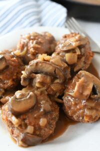 Salisbury Steak in a Muffin Pan Recipe. Mini Salisbury steak patties are served with mushroom gravy on a white plate.