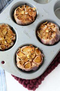 Roasted garlic in a silver muffin tin.