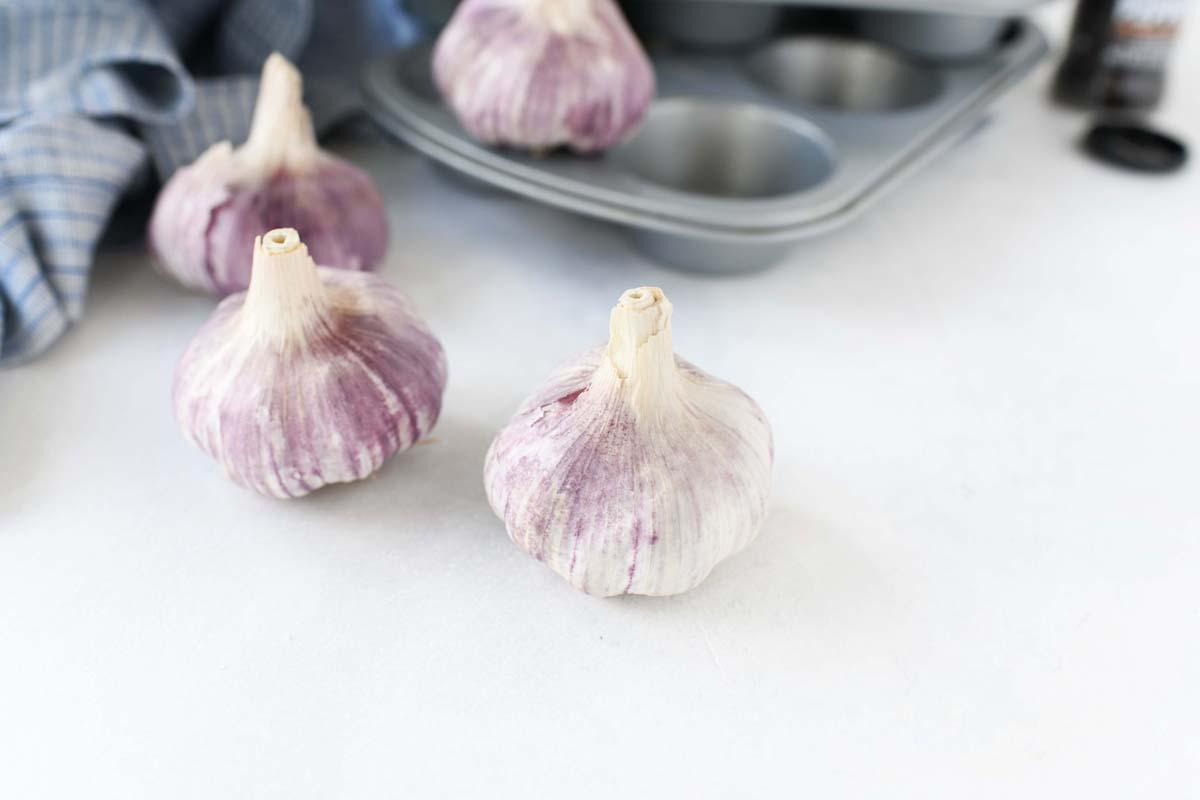 Purple Garlic bulbs near a silver muffin tin.