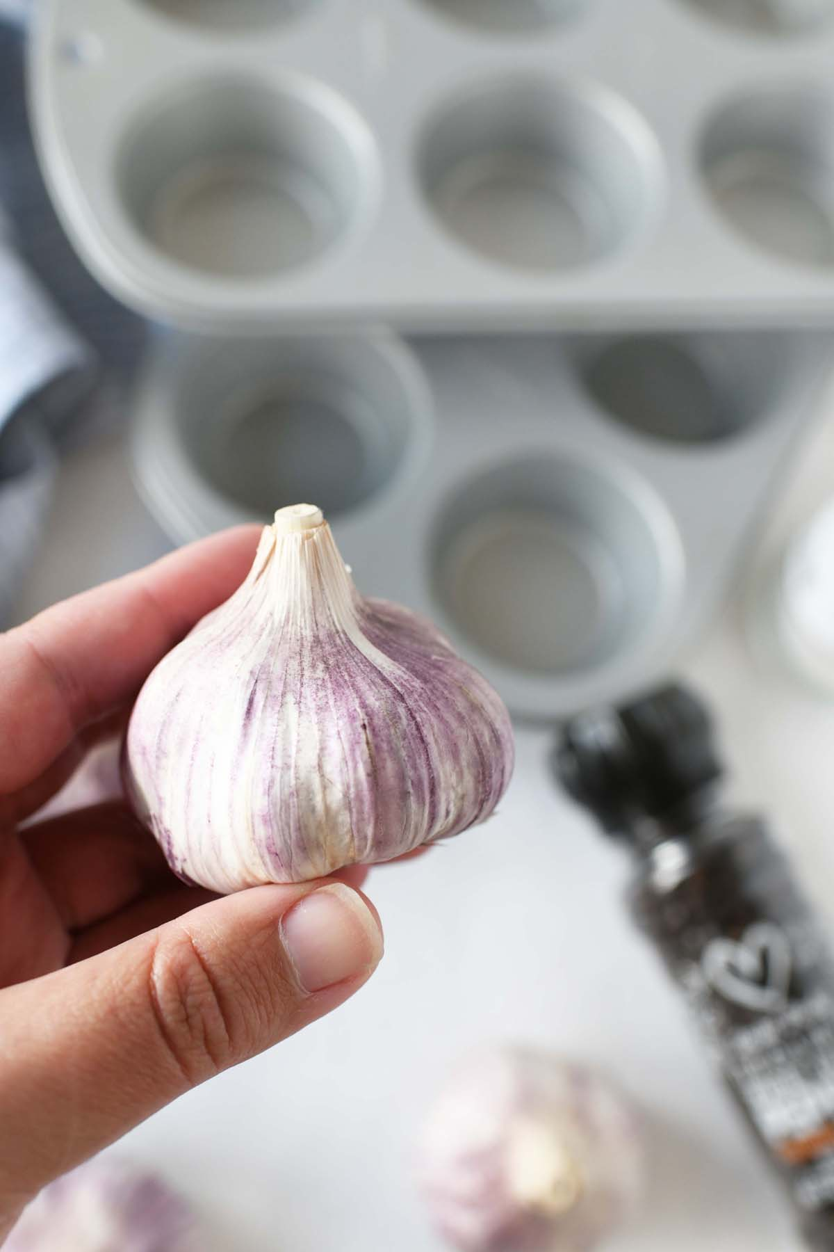 Whole Roasted Garlic in a white hand.